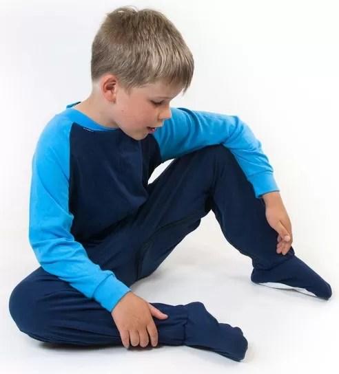 Young boy sat down wearing Seenin children's turquoise and navy zip sleepsuit