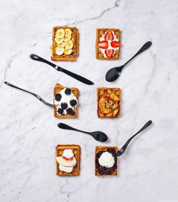 Image is a photograph of 6 square plates of food on a marble surface with Matt Black Knork cutlery