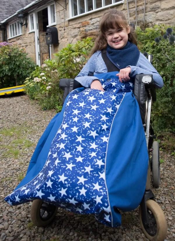 Disabled girl in navy star print Seenin waterproof wheelchair leg cover