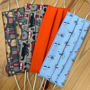 Image is a photograph of four fabric face masks, laying flat on a wooden table top. Each mask has a different design, including New York, London, plain orange and Aviation