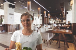 Image is a photograph of a young woman in a white t-shirt smiling to the camera. In her hand she carries a tray of plated meals ready to serve to the people in the restaurant that can be seen in the background behind her.