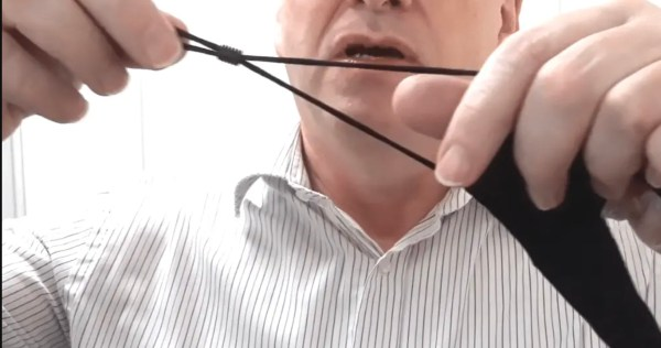 Image is a photograph of a middle-aged man stretching the ear straps of the lip reading mask and adjusting the length using the plastic ferrule