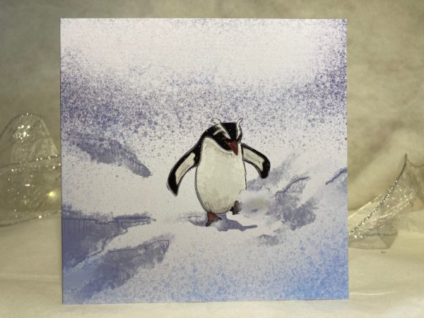 Image is a photograph of an illustrated christmas card featuring a penguin playfully kicking through the snow.