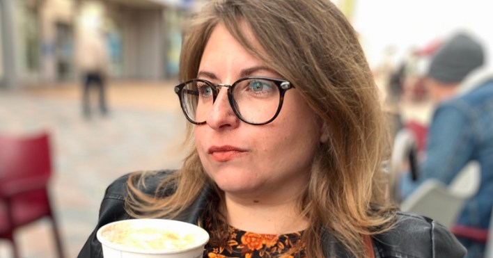 Disabled entrepreneur Carina holding a cup of coffee sitting outsied a cafe looking into the distance wearing glasses