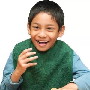 Young boy smiling wearing a green Seenin apron over a blue shirt