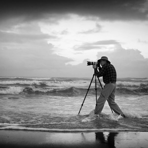 Photographer Ian Mckenzie photographedstandinig in surf with camera and tripod while leadiing an Excitations PhotoAdventures workshop. Black and white photo.