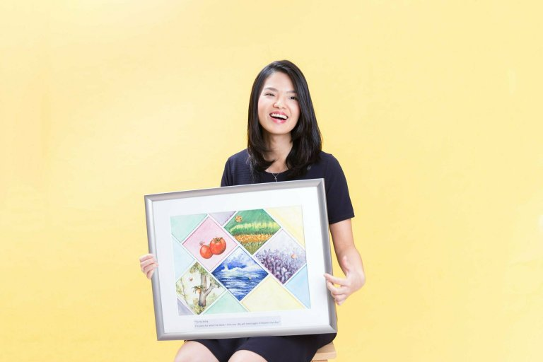 June holding an framed painting with crafted buttons