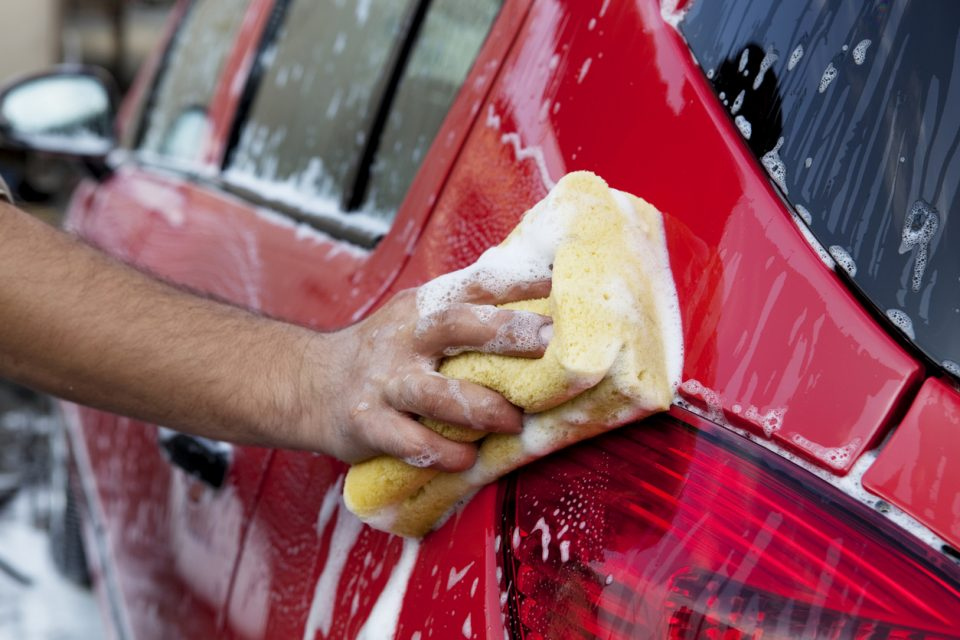 Handwashing a red car with soap and sponge