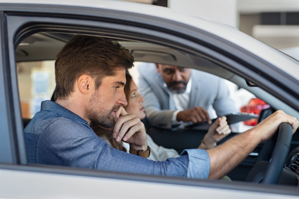 A couple sitting inside a vehicle at a car dealership