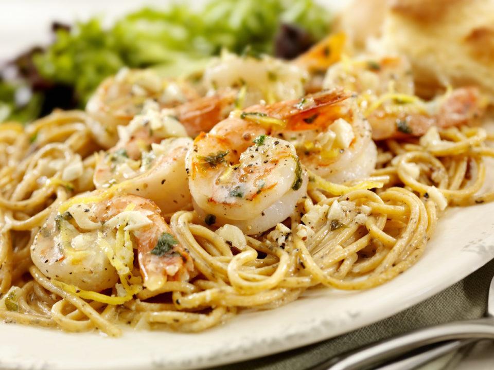 Shrimp scampi over pasta on a dinner plate