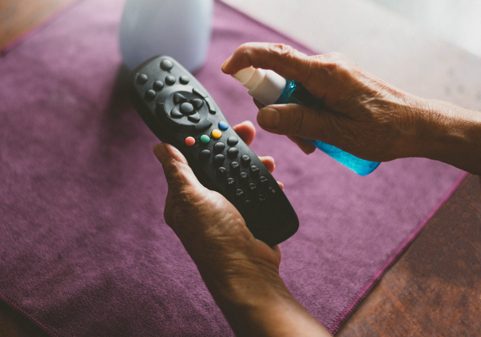 Woman spraying remote control to clean it