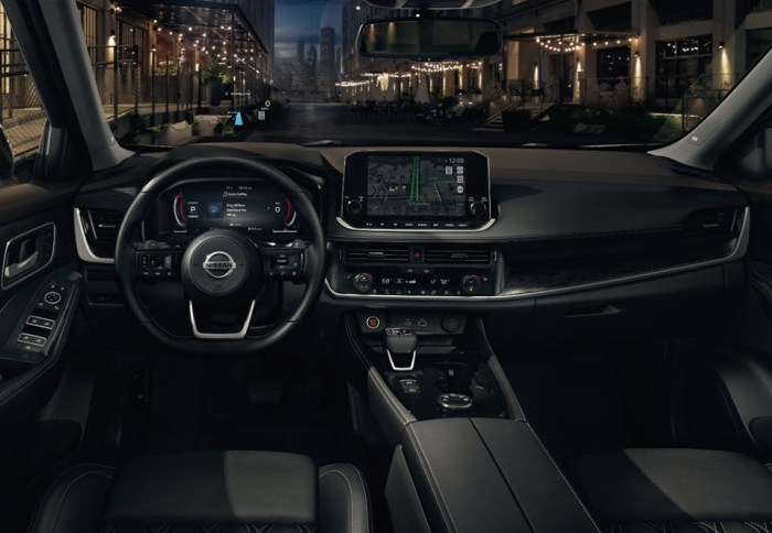 The infotainment system of the 2021 Nissan Rogue at night. The navigation system is running and the digital gauges show Apple CarPlay.