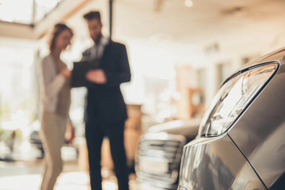 Woman shopping for a vehicle with dealership salesperson