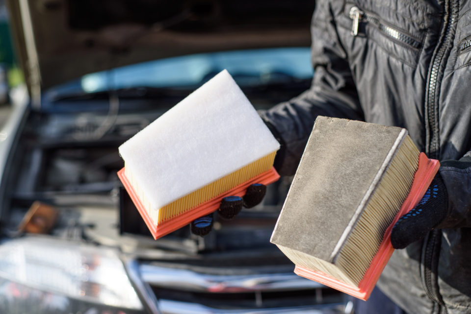 Man replaces a dirty air filter for a new one in a car.
