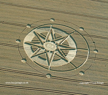 Haselor, Warwickshire. - 20th July 2015. Wheat. c.150ft (46m) An eight-pointed interlaced star with inverted triangles between its points within a flattened circle of wheat, eccentrically placed within a circle so creating a crescent. A second finer and concentric circle intersects eight circular 'satellites'. A single smaller 'satellite' lies between two of the larger ones.