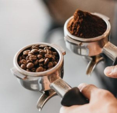 Coffee beans and ground coffee in two separate espresso portafilters