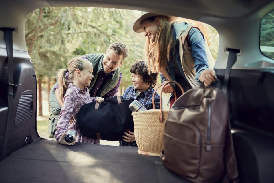 A young family organizing the back of their SUV.