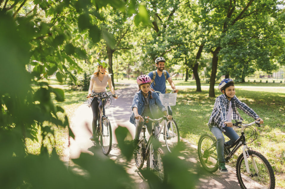 Family riding bikes on a wooded park path