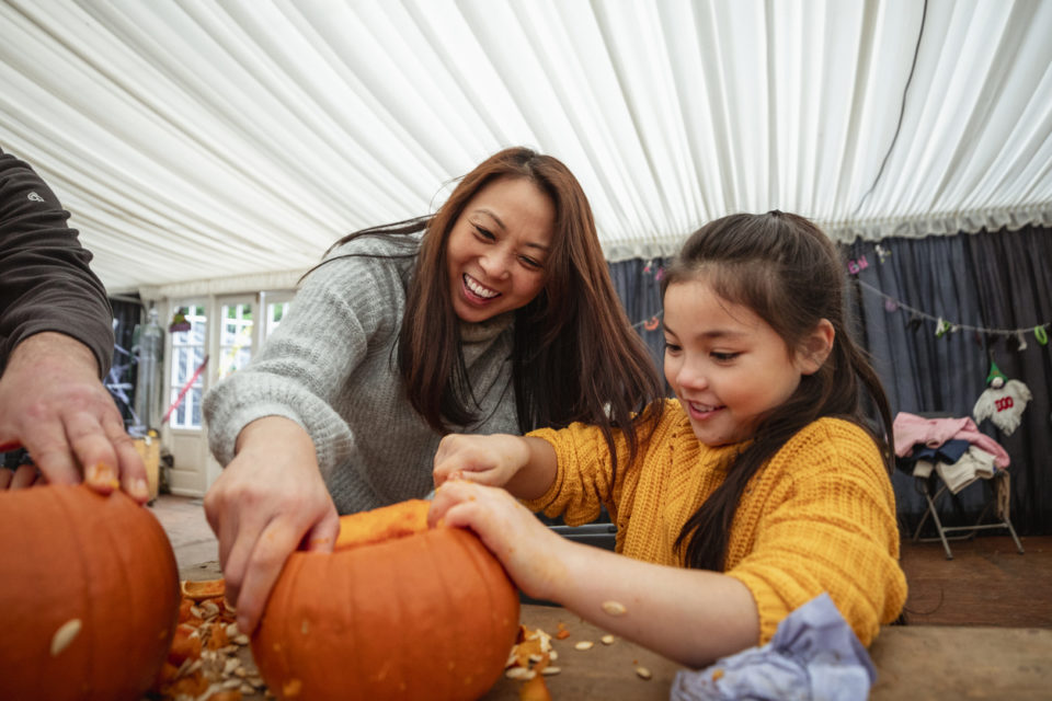 Mother and daughter carving pumpkins at a farm