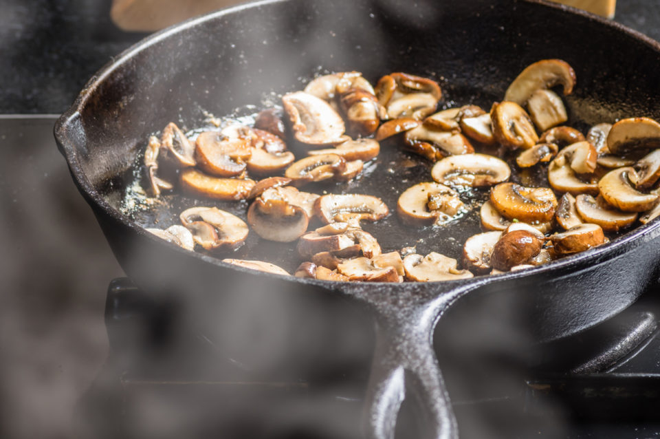 Sautéing sliced mushrooms in a skillet