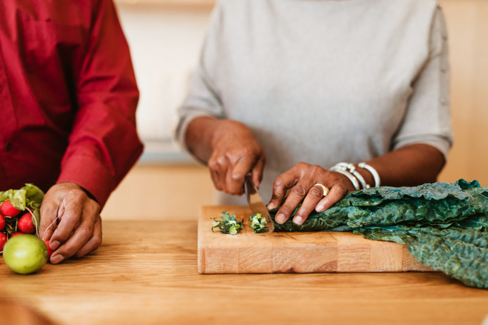 Woman chopping chard on cutting board by husband