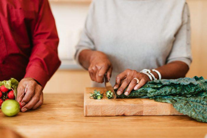Woman chopping chard on cutting board by husband
