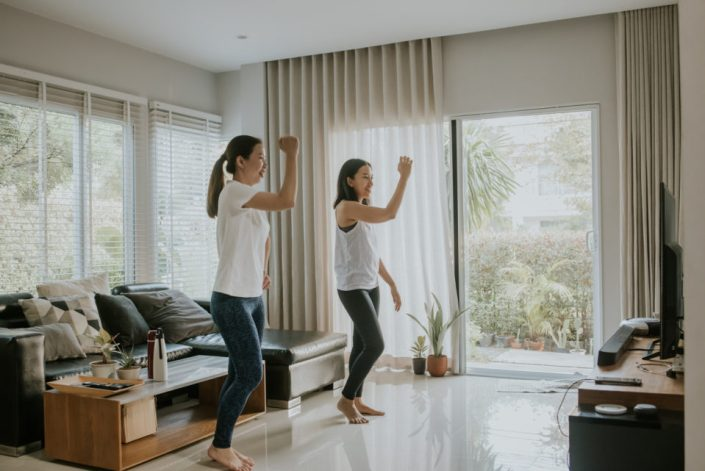 Two women doing a dance workout in their living room