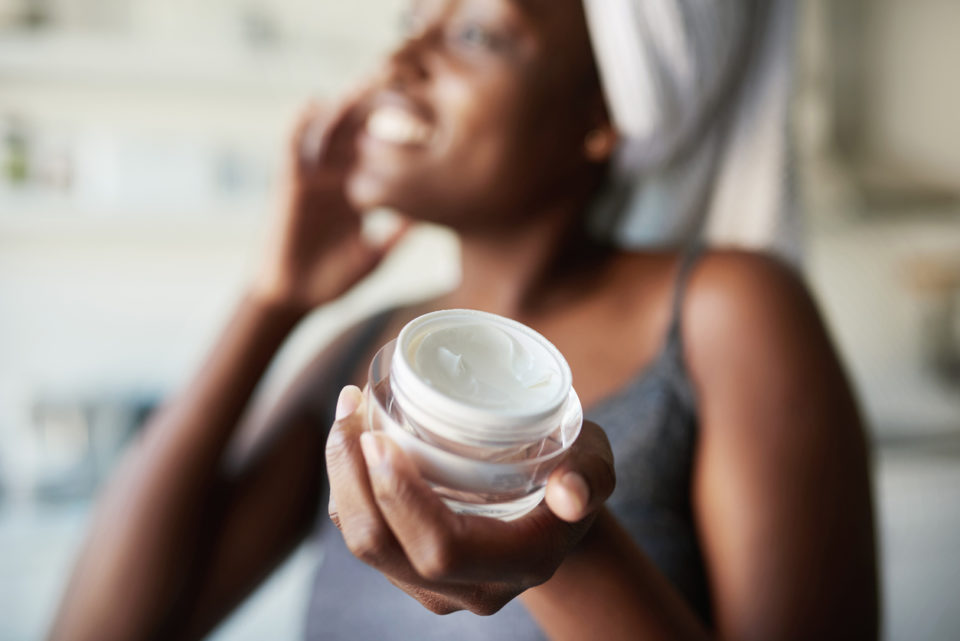 Woman holding up a face cream product