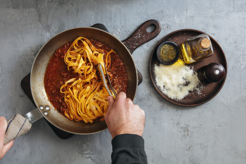 Man Cooking Classic Tagliatelle with Sauce Bolognese