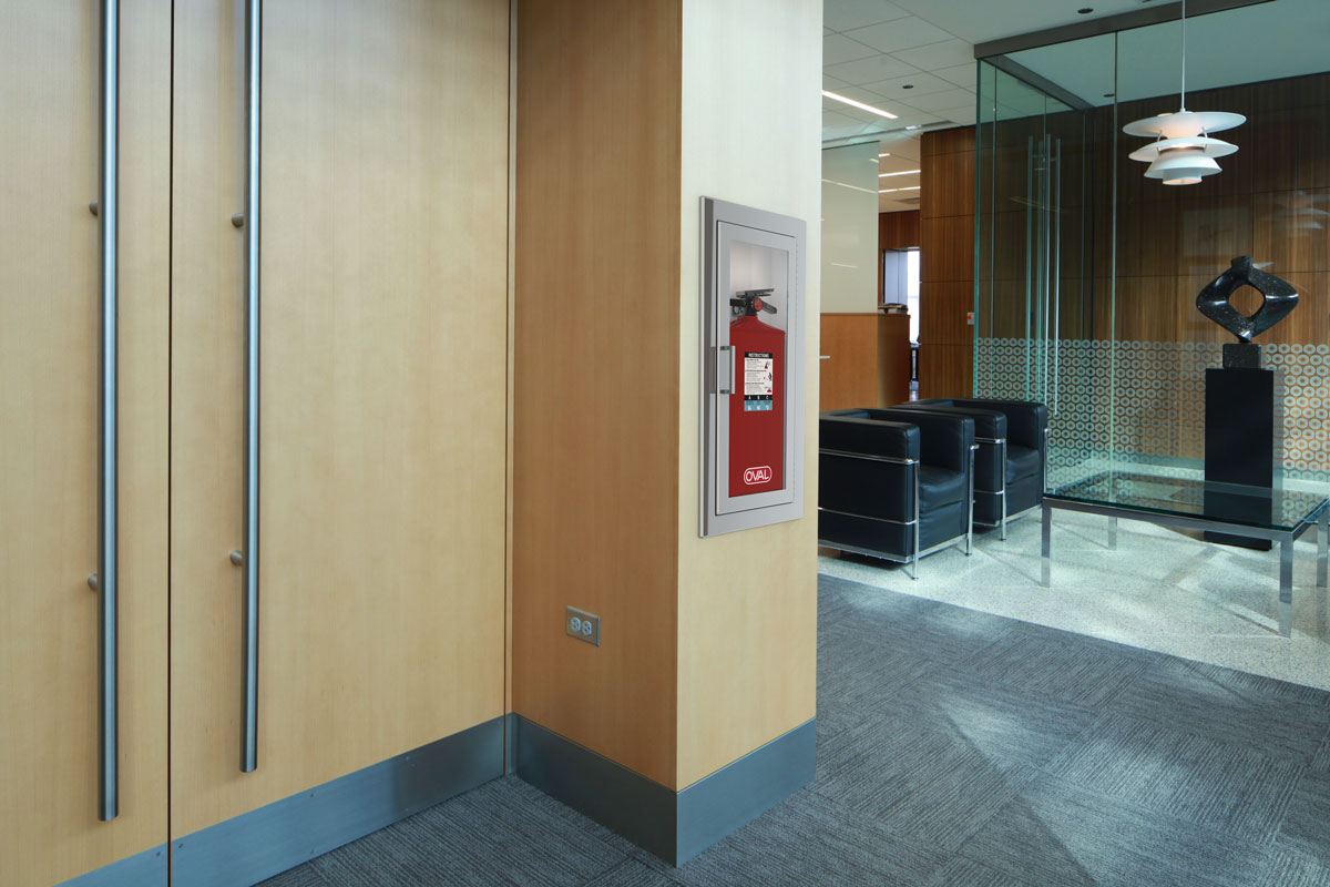 Oval Brand Fire Extinguisher Model 10JABC installed in a Second Floor Reception - White Cabinet