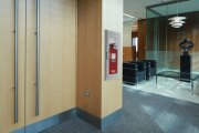 Oval Brand Fire Extinguisher Model 10JABC installed in a Second Floor Reception – White Cabinet