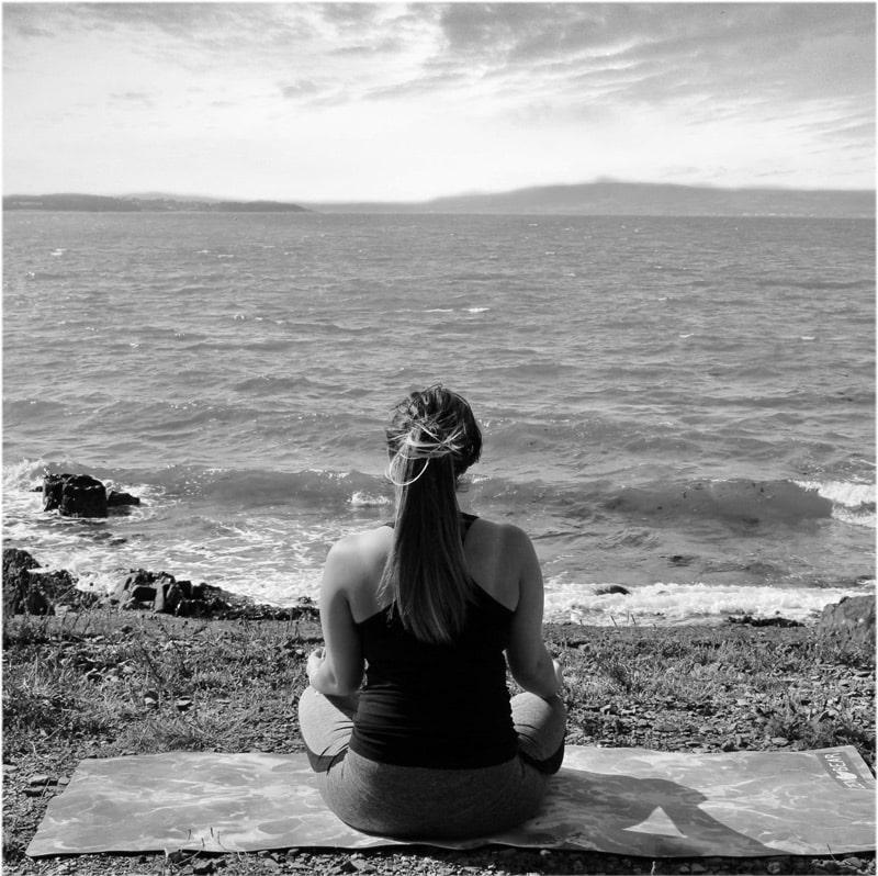 Vrouw die aan het mediteren is op haar yoga mat bij de zee