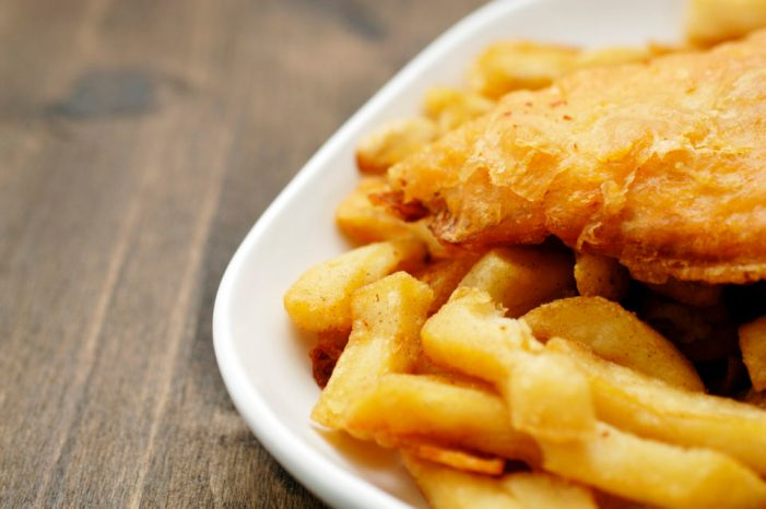 Fried fish and fries on a white plate