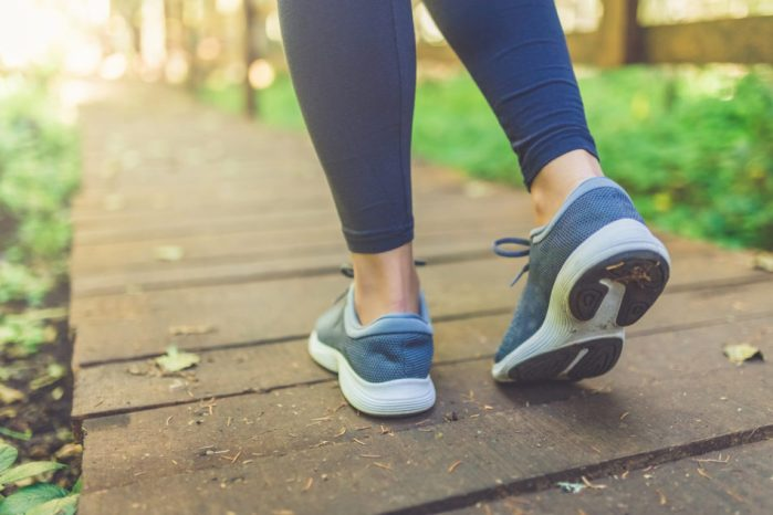 Close up of a female walking on a trail and wearing tennis shoes