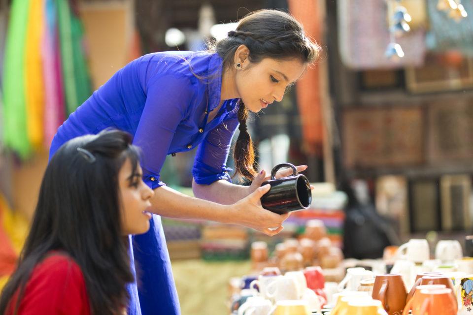 Women shopping for porcelain jug at street market
