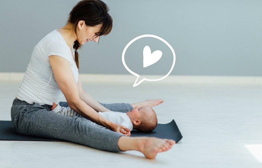 ヨガマットの上に足を開いて座り、赤ちゃんをその間に寝かせる女性