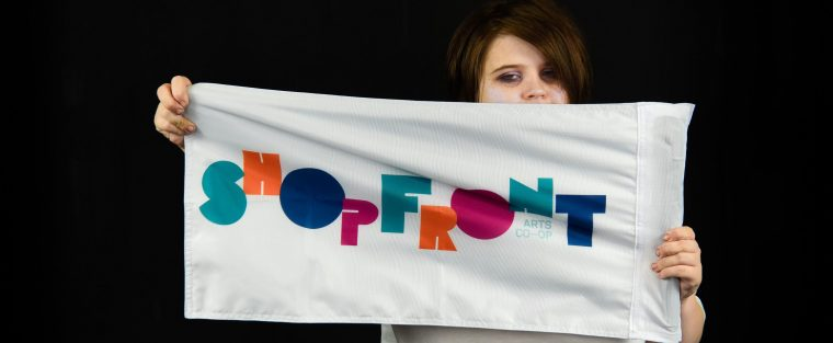 Image description: A black background with a person standing centre. They are holding a flag with the Shopfront Arts Co-op logo on it up in front of them. They have dark hair and eye makeup on.