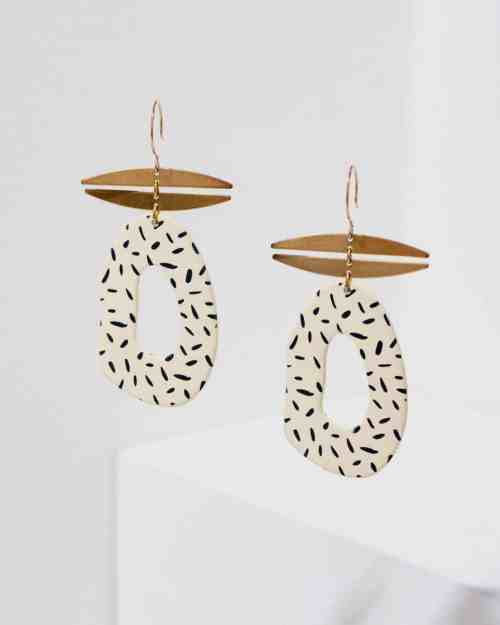 Brass earrings with dotted cream pendants hanging from them