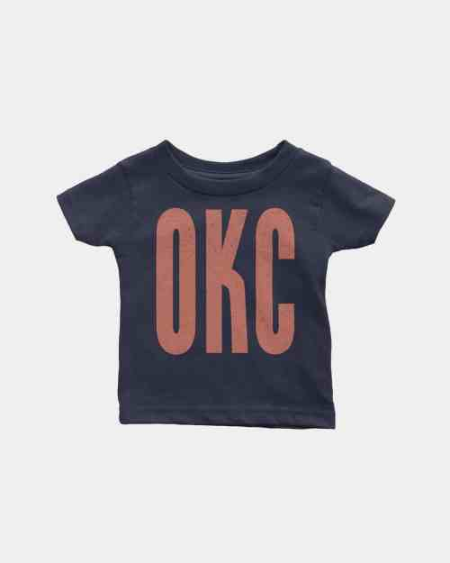 A mockup of a navy blue kids tee shirt that says OKC in coral ink