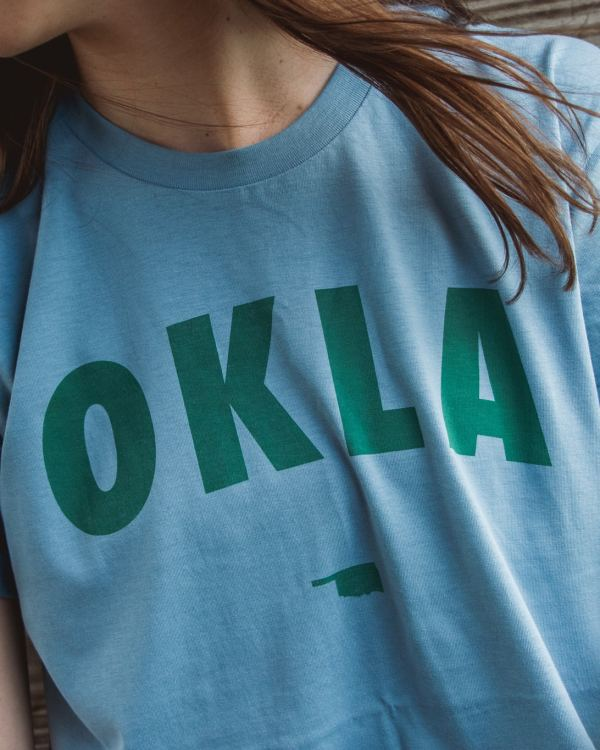 A woman wearing a blue shirt that says OKLA across the front in turquoise ink