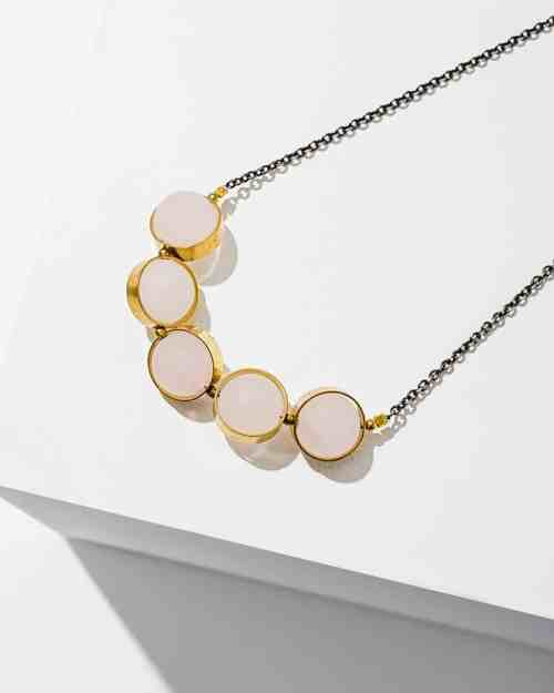 A brass necklace with rose quartz stones on the end