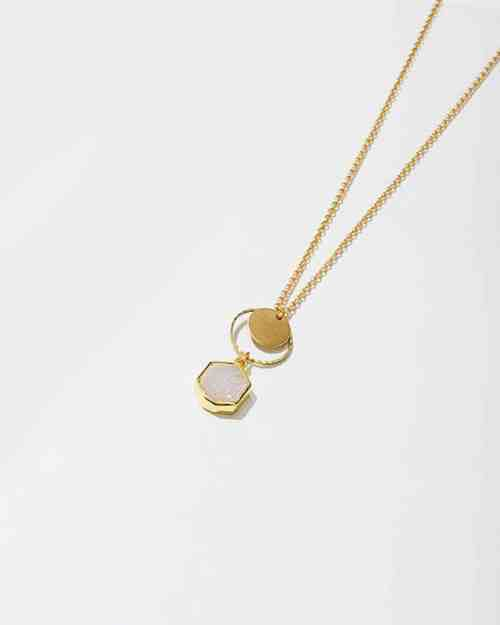 A brass necklace with a white stone on the bottom