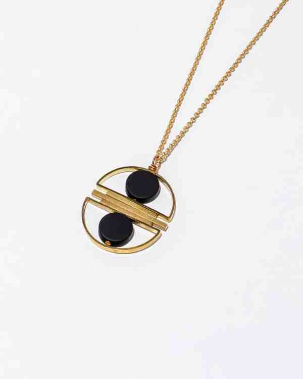 A brass necklace with two onyx stones in between a halo