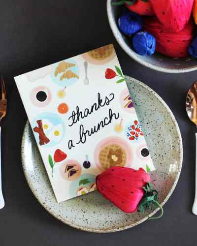 A white, paper card that says 'Thanks a brunch,' surrounded by foods