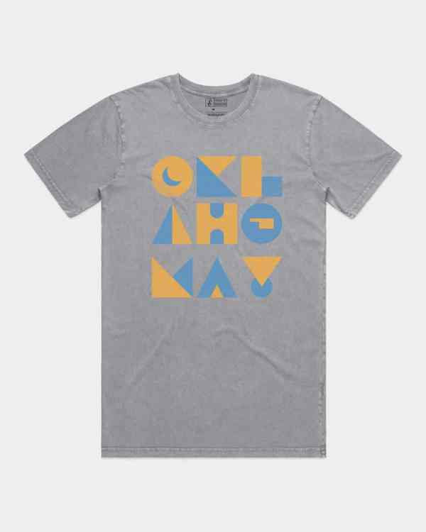 A mockup of a grey tee shirt that says Oklahoma in yellow and blue ink. The letters are made out of geometric shapes.
