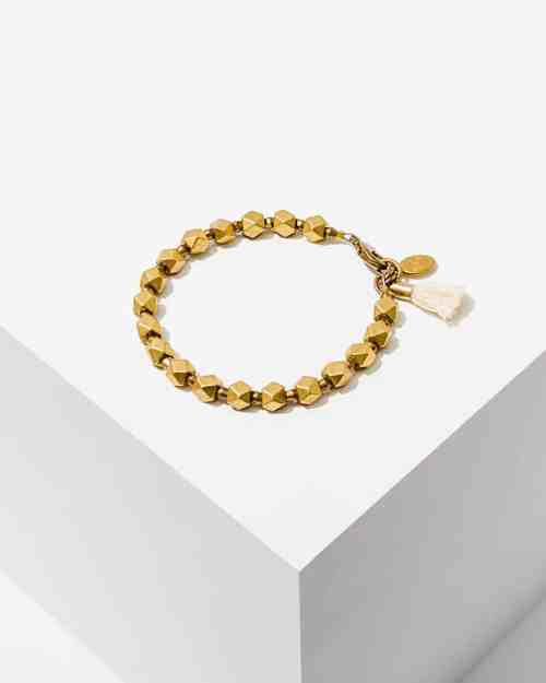 A brass stone bracelet with an ivory feather accent