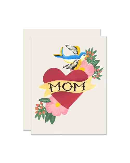 A white paper card with a heart on the front that says Mom.