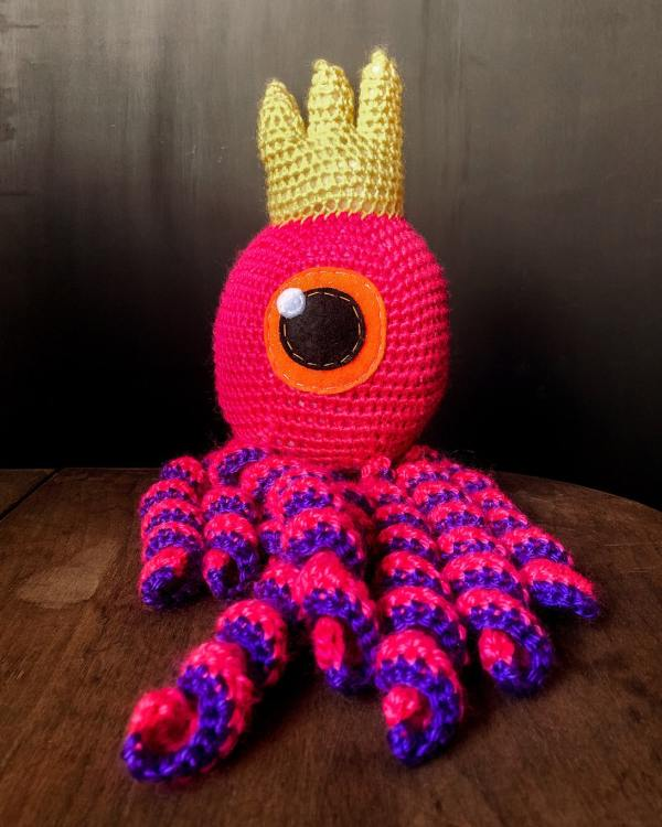 A pink big eye moster kid's toy that's handknitted