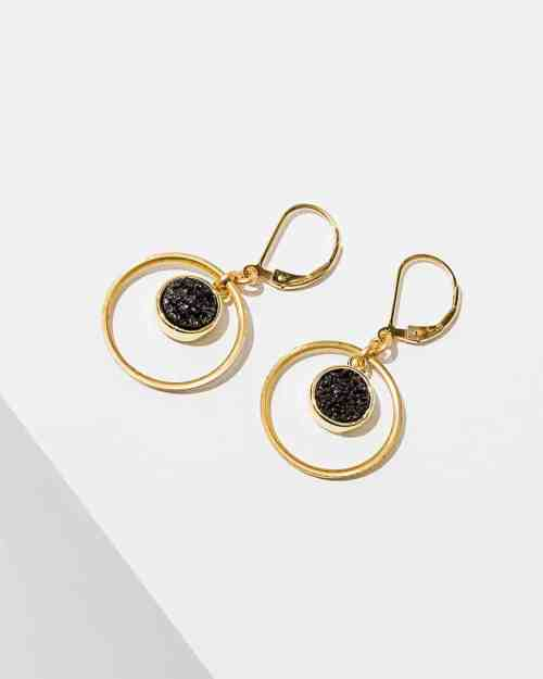 A photo of gold kamilah earrings with black center stones