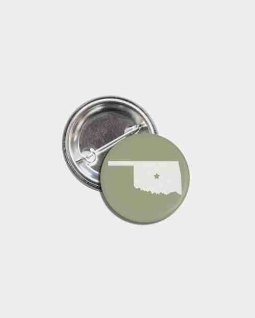 A green tin pinback button with the state of Oklahoma on it in white.